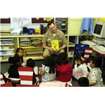 Naval Officer reading Dr. Seuss to elementary school students.