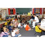 1 Mess Management Specialist Gui Gagui, Armed Forces Committee Chairperson, reads a book to a group of 1st grade students at E J King Elementary School