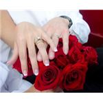 Hands laid on a red rose bouquet