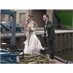 Newly-wed couple stand on the bow of a boat.