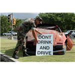 U.S. Navy Master-at-Arms 1st Class Robert C. Tempesta places a ^ldquo,Don^rsquo,t Drink and Drive^rdquo, sign in front of a wrecked car outside the front gate of U.S. Naval Base Guam