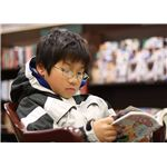 1024px-Young boy reading manga
