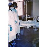 1976 photograph shows two nurses standing in front of Ebola case #3, who was treated, and later died at Ngaliema Hospital, in Kinshasa, Zaire - Image released into the public domain by the Centers for Disease Control and Prevention