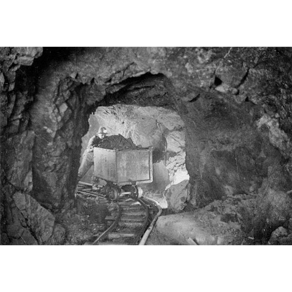 A miner hauling a car of silver radium ore, 340 feet below the surface, Eldorado Mine of Great Bear Lake