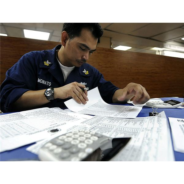 795px-US Navy 091028-N-7280V-170 Culinary Specialist 1st Class Neil Monato verifies figures on a food preparation worksheet while underway aboard the amphibious command ship USS Blue Ridge (LCC 19)