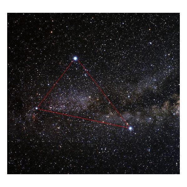 The asterism of the Summer Triangle composed of the three bright stars Vega (top left), Altair (lower middle) and Deneb (far left)