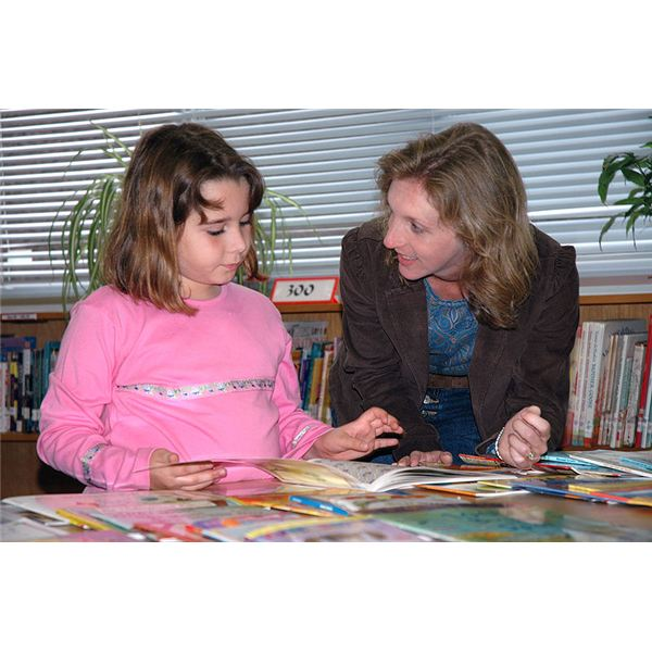 Jennifer Tonder (right), a teacher's aide for a 3rd-4th grade multi-age class, discusses the various books available from the Reading Is Fundamental (RIF) grant given to Sasebo Elementary School with