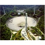 The enormous dish of the Arecibo Observatory. The reflector is suspended 450 feet above the dish and weighs roughly 900 tons; suspending this platform are large cables strung from the reinforced concrete pillars, one 365 feet tall, the other two 265 feet tall.