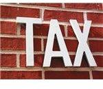 Tax written on brick wall