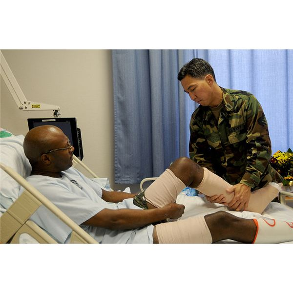 Physical therapist Lt. Cmdr. Mitchel Ideue, Officer in Charge of Inpatient Services at Landstuhl Regional Medical Center, in Landstuhl, Germany, gives Army Sgt. Charlie McCall a physical therapy trea