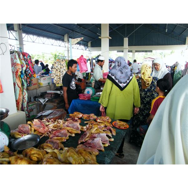 Observe the outfits of several women buying chickens, as well as the scarves and skirts for sale.