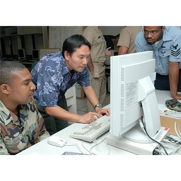 Matt Inaki, computer network defender coach-trainer of SPAWAR Systems Center San Diego, shows how to monitor the activity of a network to Air Force Staff Sgt. Daryl Graham and Information Systems Tech