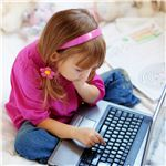Young girl typing on a laptop computer