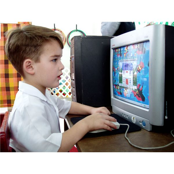 Child playing educational game on computer.