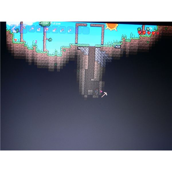 Digging below the surface in Terraria to find ore that'll help craft some equipment when starting out.