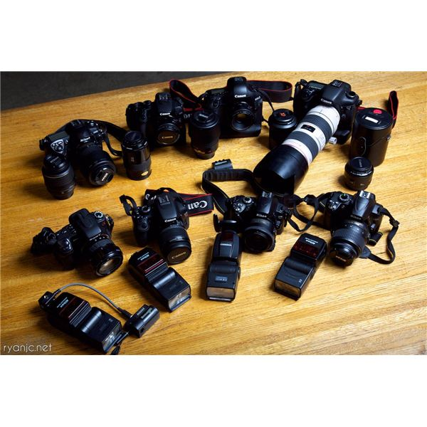 table full of cameras, lenses, and photographic gear
