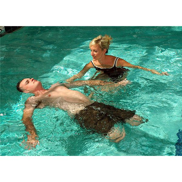 Lynn A. Boulanger, a Naval Medical Center San Diego occupational therapist, assists Marine Corps Staff Sgt. Jesse A. Cottle, a bilateral amputee,