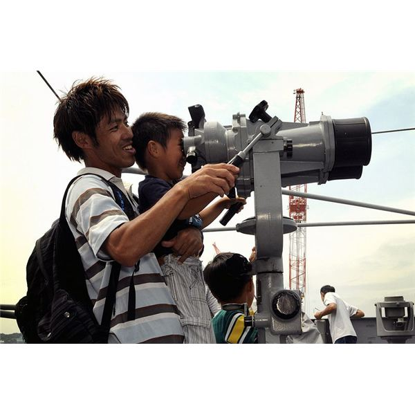 A father picks up his son to look through binoculars.